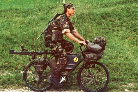 Ein Soldat, ausgerüstet mit Waffen und Gepäck, fährt mit einem der neuen Dienstfahrräder der Schweizer Armee. Aufgenommen am 21. Juli 1991.