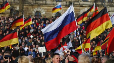 Supporters-of-the-anti-Islam-movement-PEGIDA-carry-German-and-Russian-flags-duri